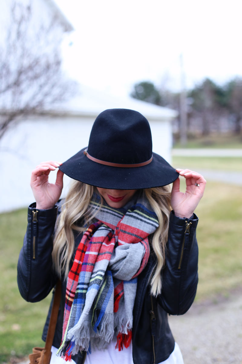 Black hat, black jacket and a plaid scarf.
