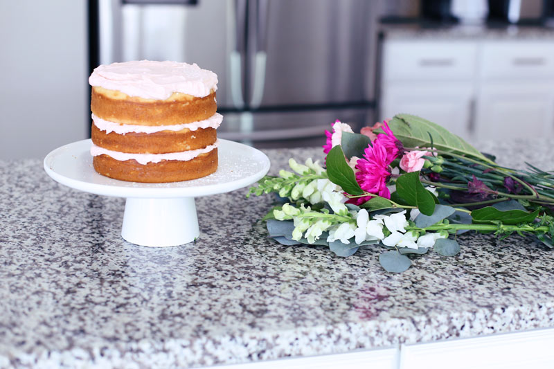 A naked cake and pink and white flowers lie on a kitchen counter. Twist Me Pretty.