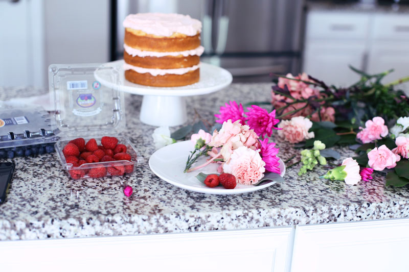 A kitchen counter decorated with berries and flowers, with a naked cake. Twist Me Pretty.