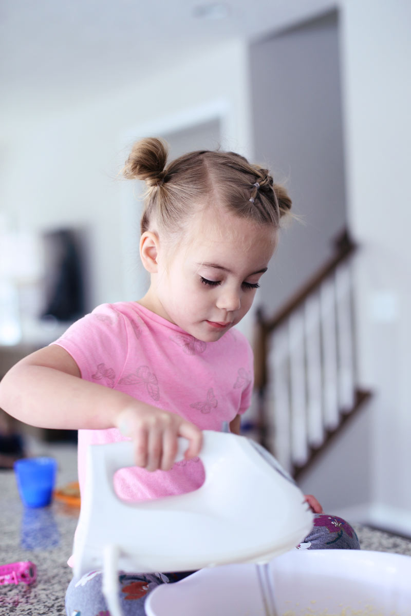 A four-year-old girl sits on a counter and uses a hand mixer to bake a cake with Twist Me Pretty.