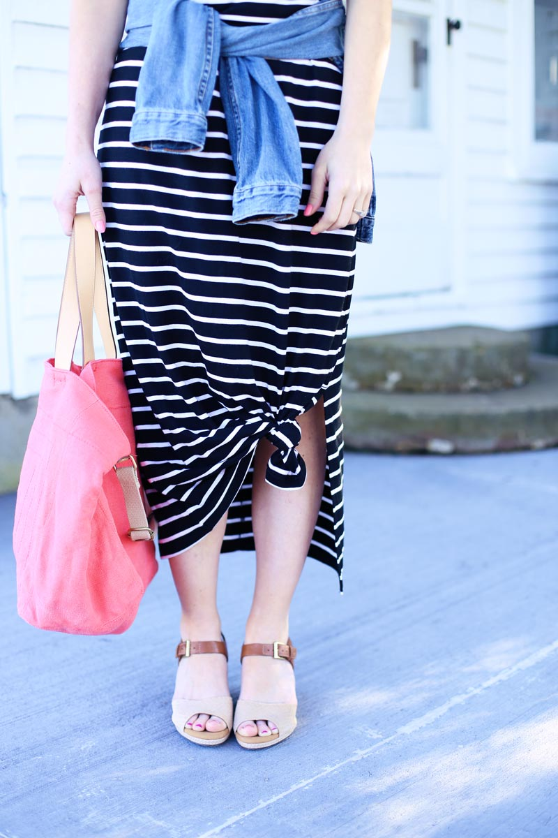 Abby wears a striped midi-dress tied in the front and a bright pink tote.