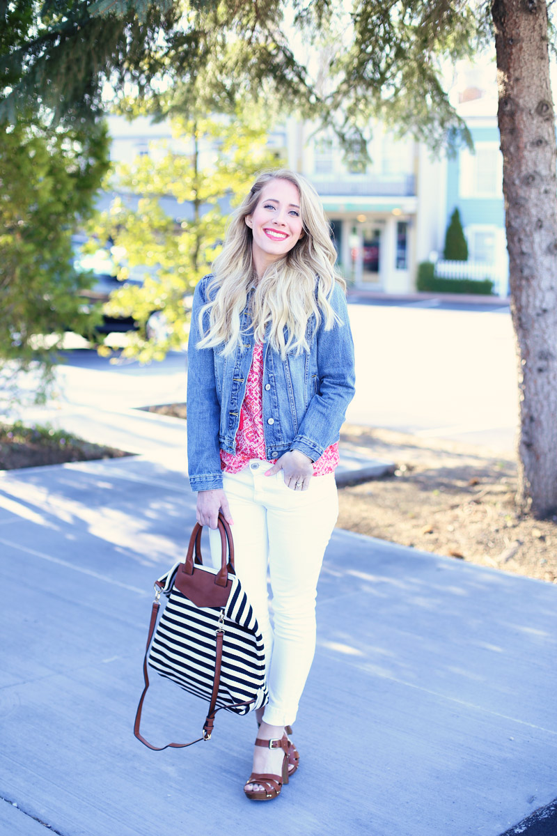 Abby wears white pants, a pink shirt, denim jacket, tan shoes and a striped bag.