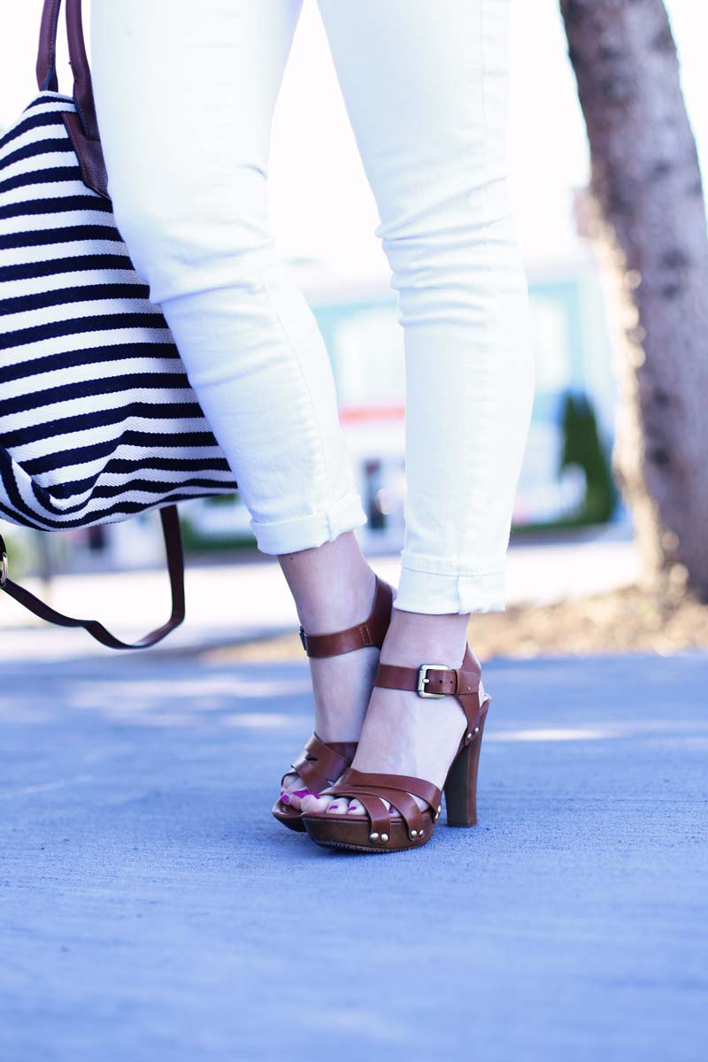 White jeans, striped oversized handbag, and brown sandals.
