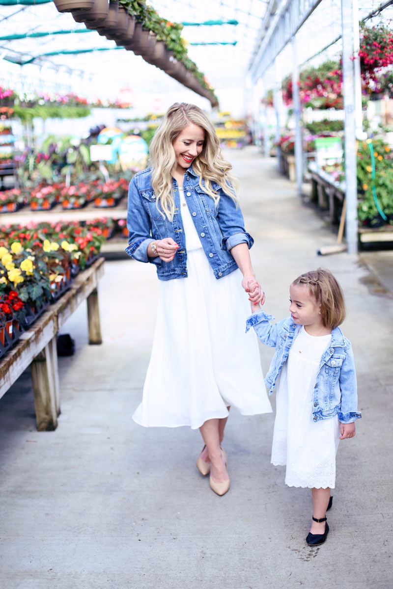 Mom and daughter explore the nursery and look at flowers