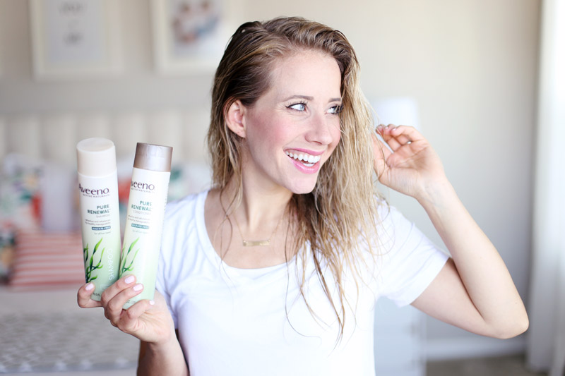Twist Me Pretty's Abby has wet hair. She smiles and holds bottles of Aveeno Pure Renewal shampoo and conditioner in one hand and touches her hair with the other.