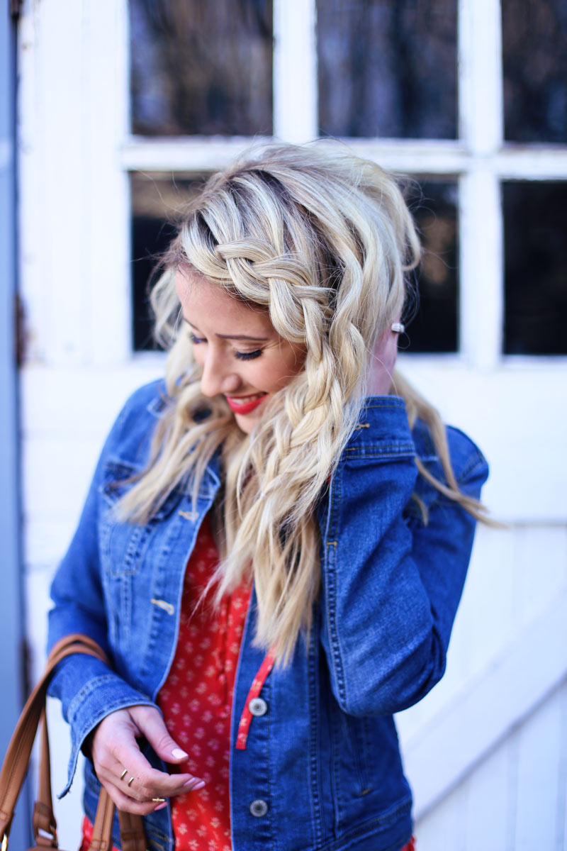 Abby, wearing a denim jacket over a red dress, smiles and holds her loose, braided hair.