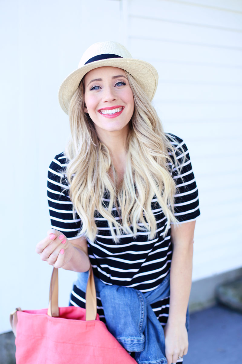 Holding a handbag and wearing a striped blue and white shirt and a wicker hat, Abby smiles at the camera as her hair cascades loosely down her shoulders.
