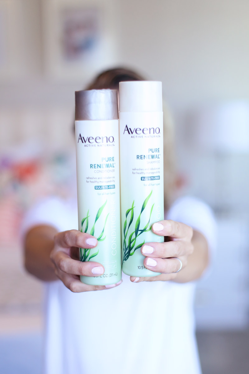 A woman holds out two bottles of Aveeno's Pure Renewal Range.