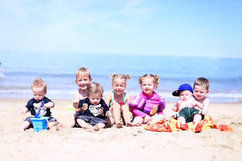 Abby's children sit with their cousins on the beach in Michigan