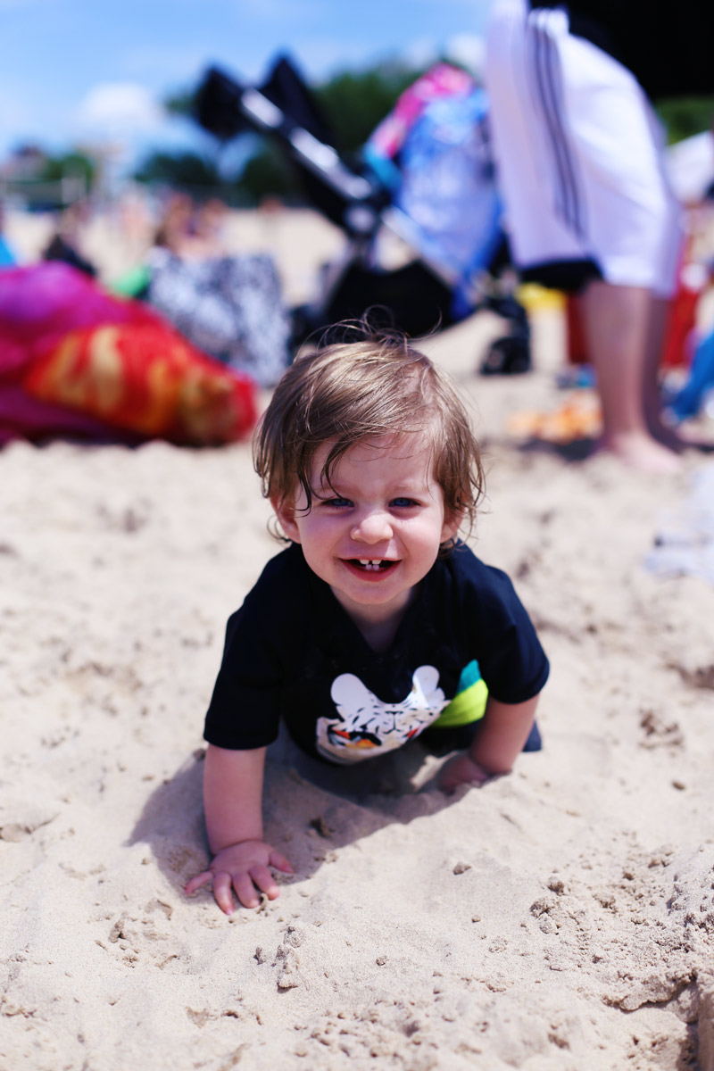 Coop crawls in the sand and grins into the camera.