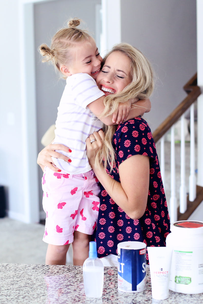 Mother daughter love. Savy and Abby hug tightly in the kitchen.