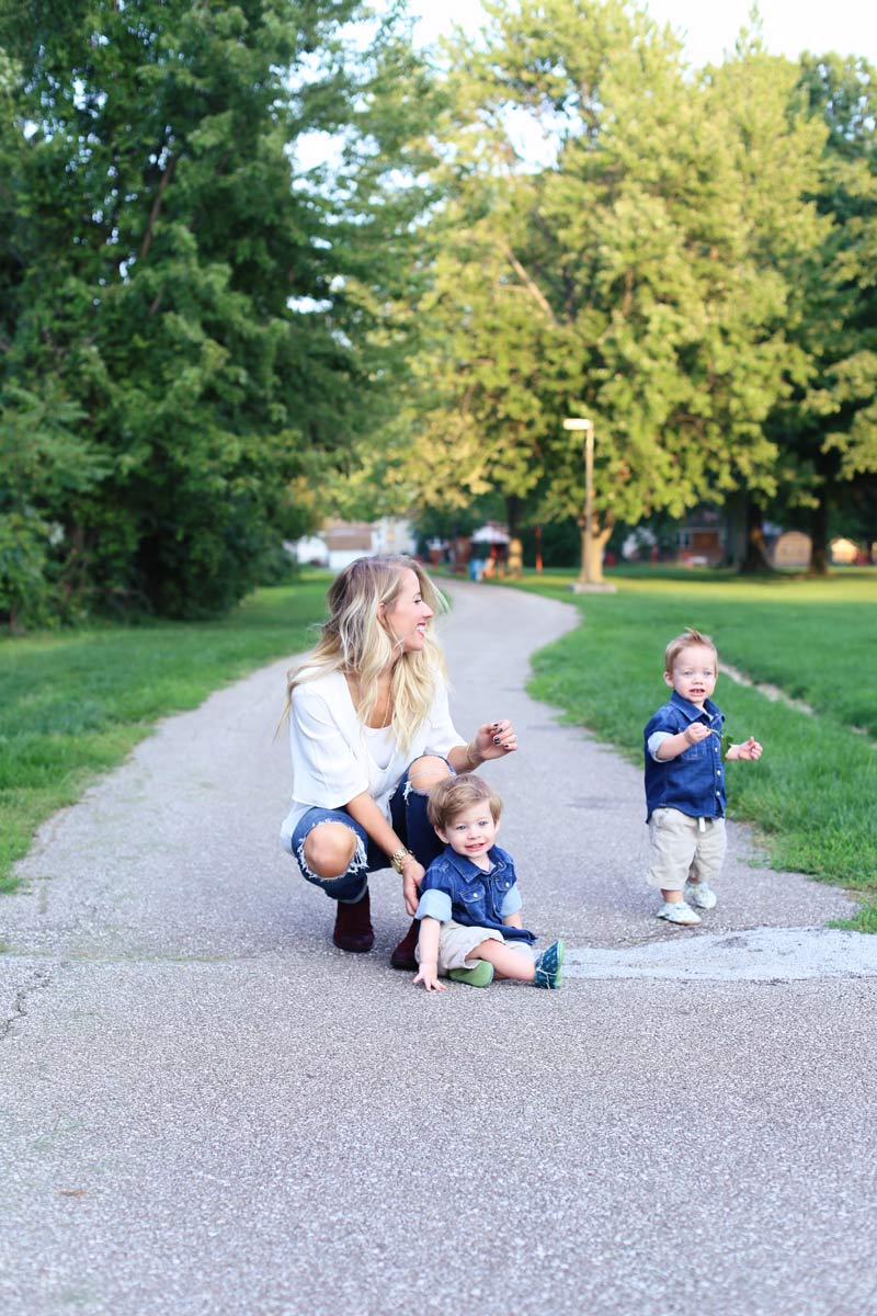 A mother bends down and smiles at her twin boys. Enjoy motherhood. Twist Me Pretty.