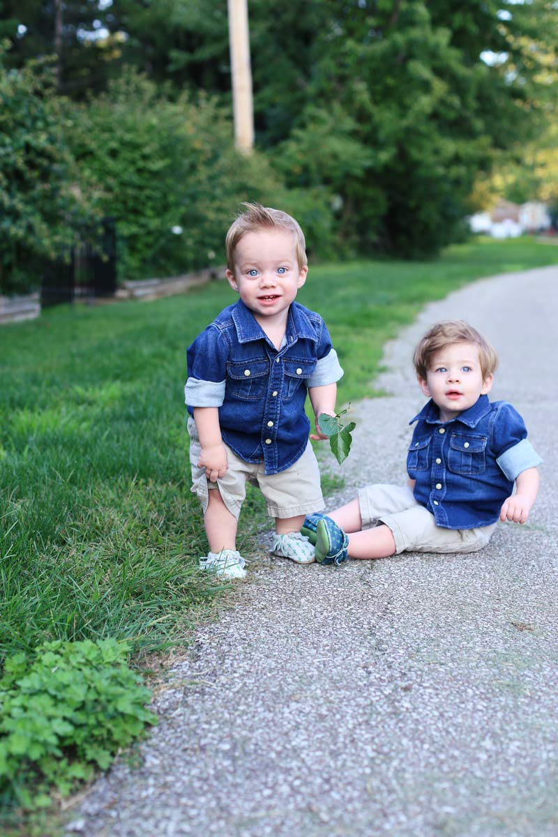 Twin boys with bright blue eyes are wearing denim jackets. One sits, one stands in the park. Enjoy motherhood. Twist Me Pretty.