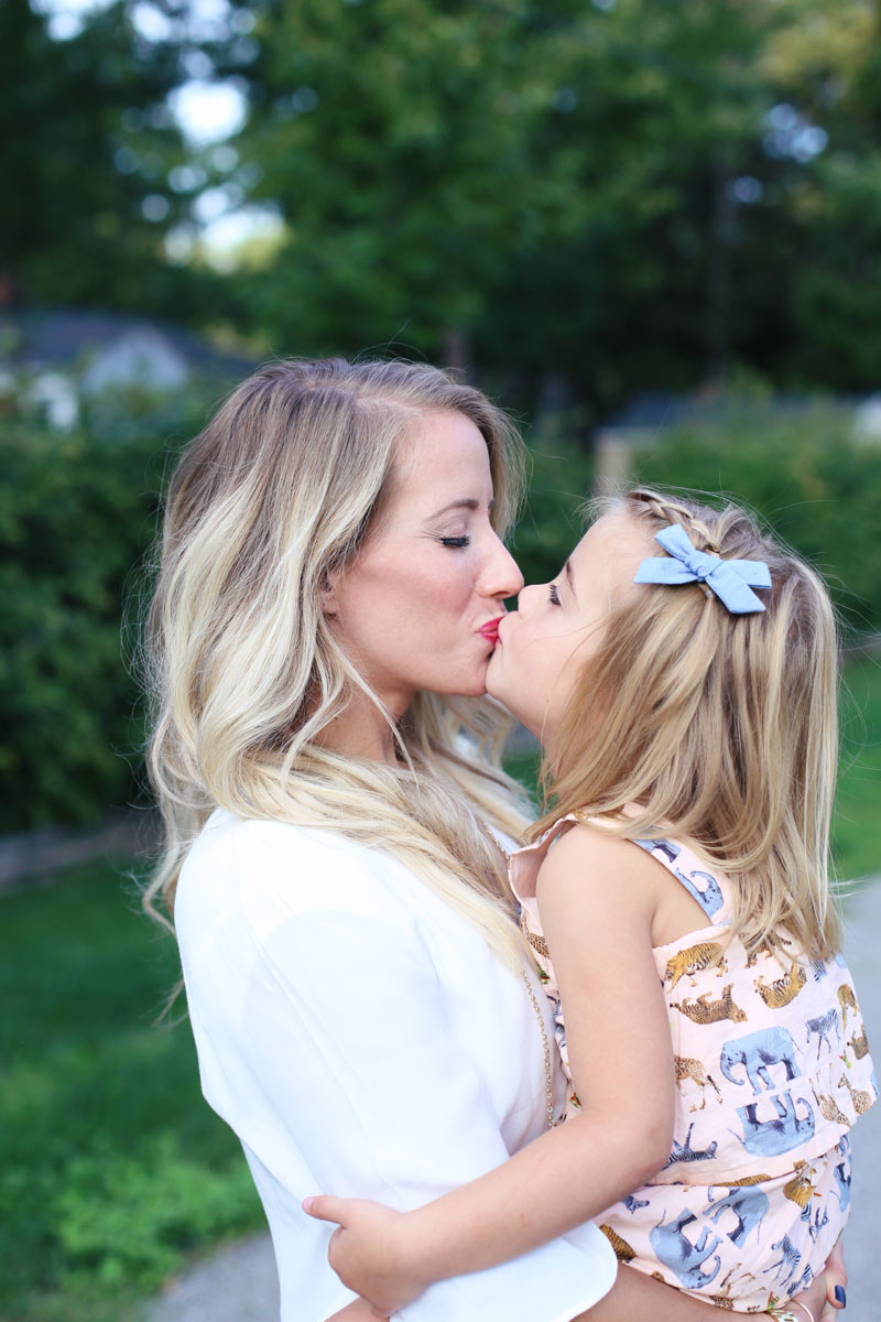 Motherly love. A mother kisses her daughter on the lips. Enjoy motherhood with Twist Me Pretty.