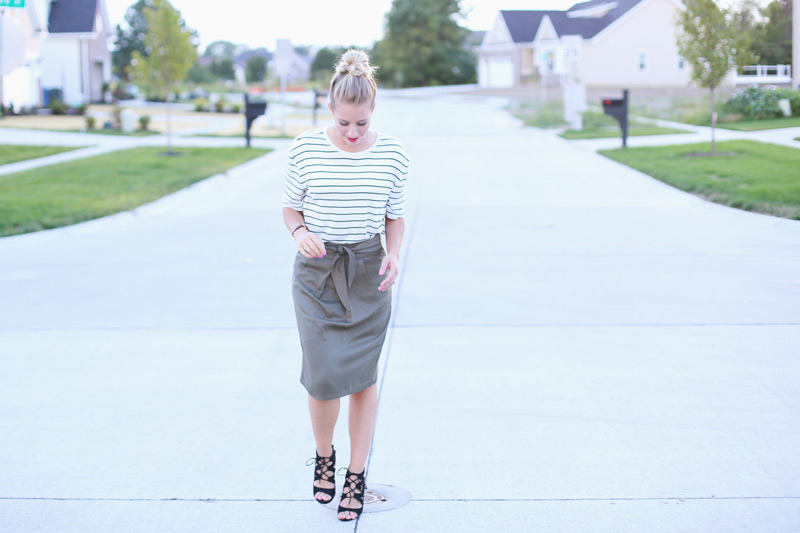 Abby walks down the road wearing a grey skirt, white striped top, and strappy sandals. Twist Me Pretty. Sunday Style.