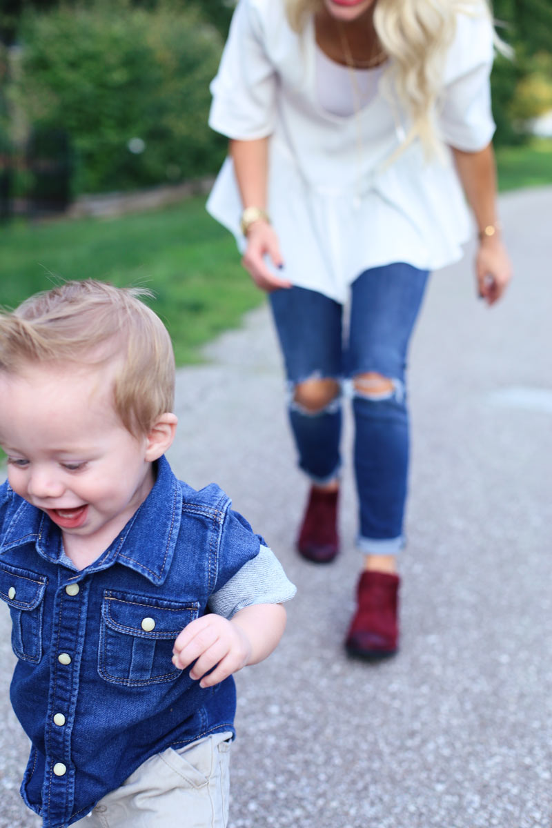 In the foreground, a baby boy runs, grinning. In the background, his mother bends slightly forward as she chases him. Enjoy Motherhood. Twist Me Pretty.
