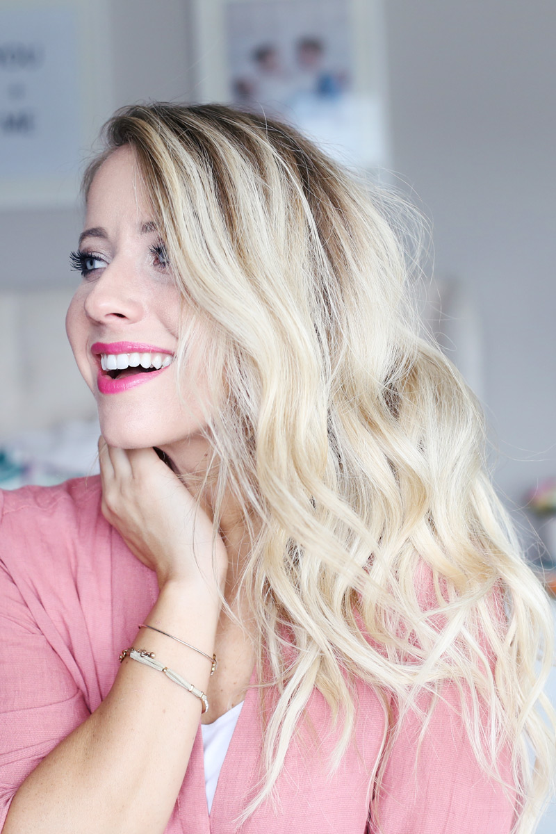 A woman wearing pink lipstick with wavy blonde hair smiles as she looks to her right. Twist Me Pretty. Find how how you can get her gorgeous hair.