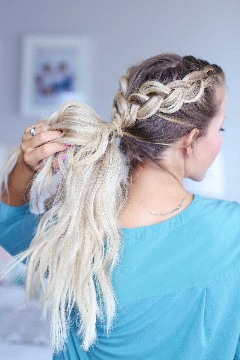 A blonde woman faces away from the camera, holding her hair, which is twisted into a dutch braid. Hair style tutorial.
