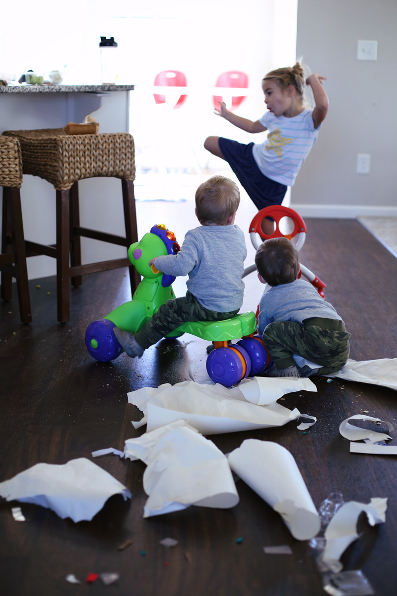 In a kitchen, two toddlers watch their older sister dance, with shredded paper in the foreground.