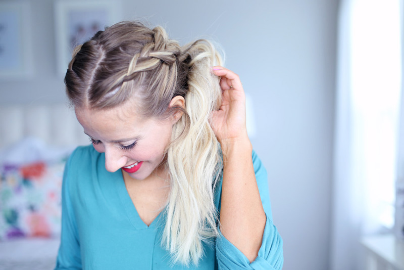 A blonde woman looks down as she holds her hair, which is styled in a dutch braid. Dutch braid hairstyles tutorial.