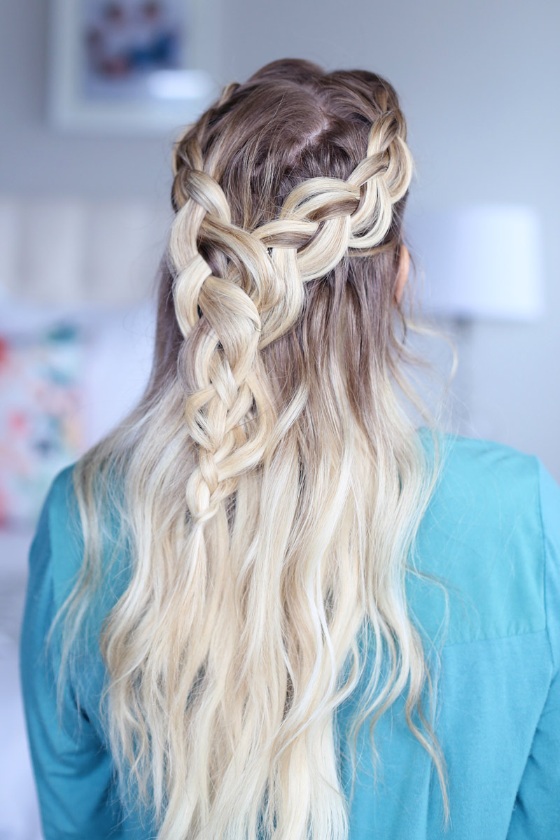 A blonde woman faces away from the camera, her hair cascading down her back. Two braids come around each side of her head and meet at the back. Dutch braid hairstyles tutorial.