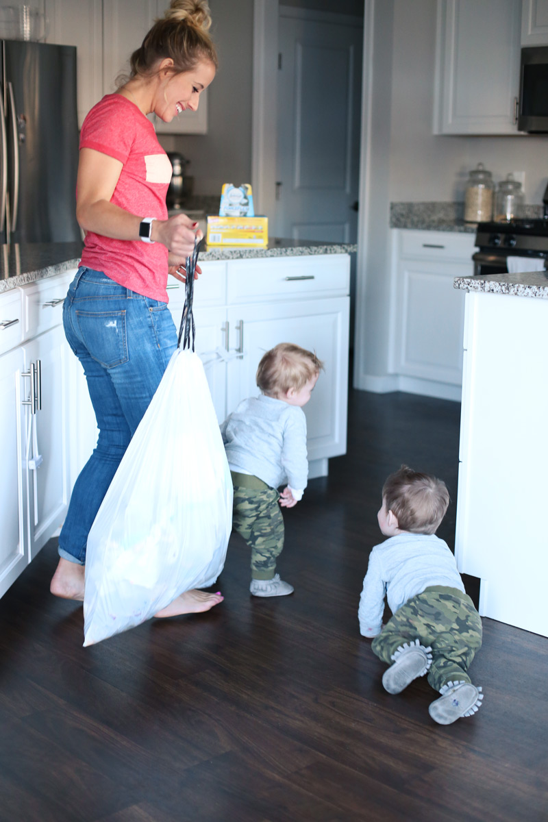 A mother happily holds a trash bag as she smiles at her two toddlers.