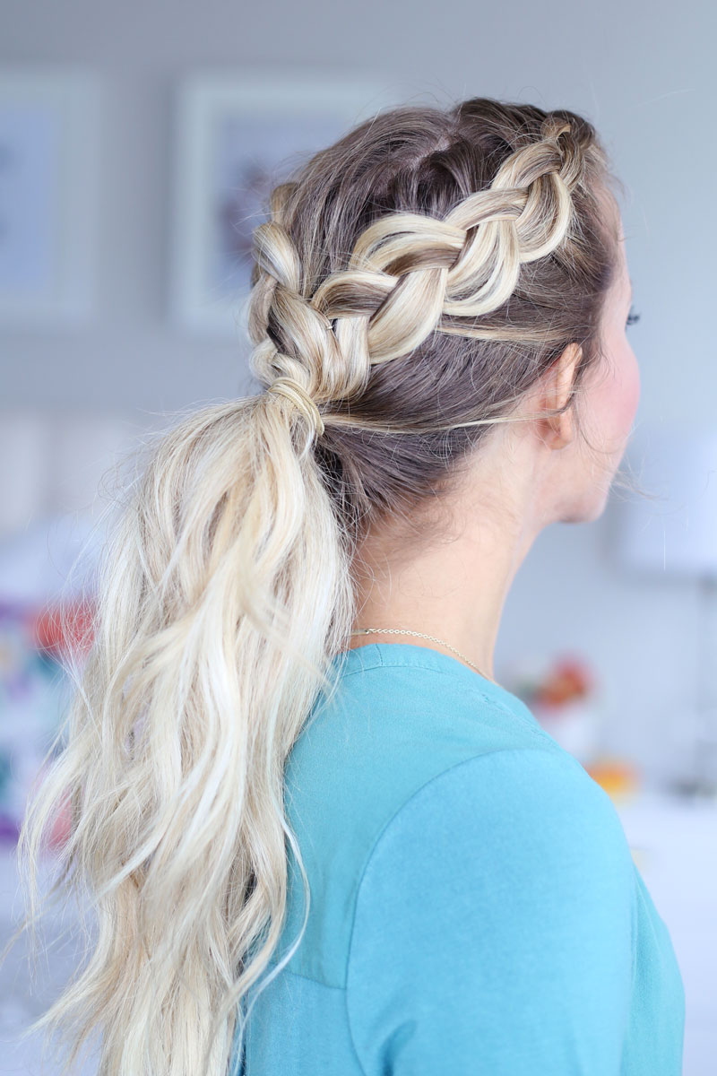 A side-view of a blonde woman with two braids, one on each side of her head. The braids meet in a long ponytail down her back. Dutch braid hairstyles tutorial.