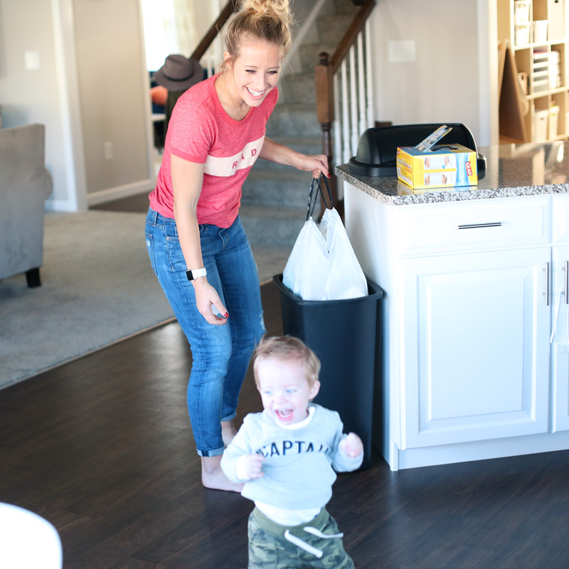 How to keep a clean kitchen? A toddler runs away from his smiling mother.