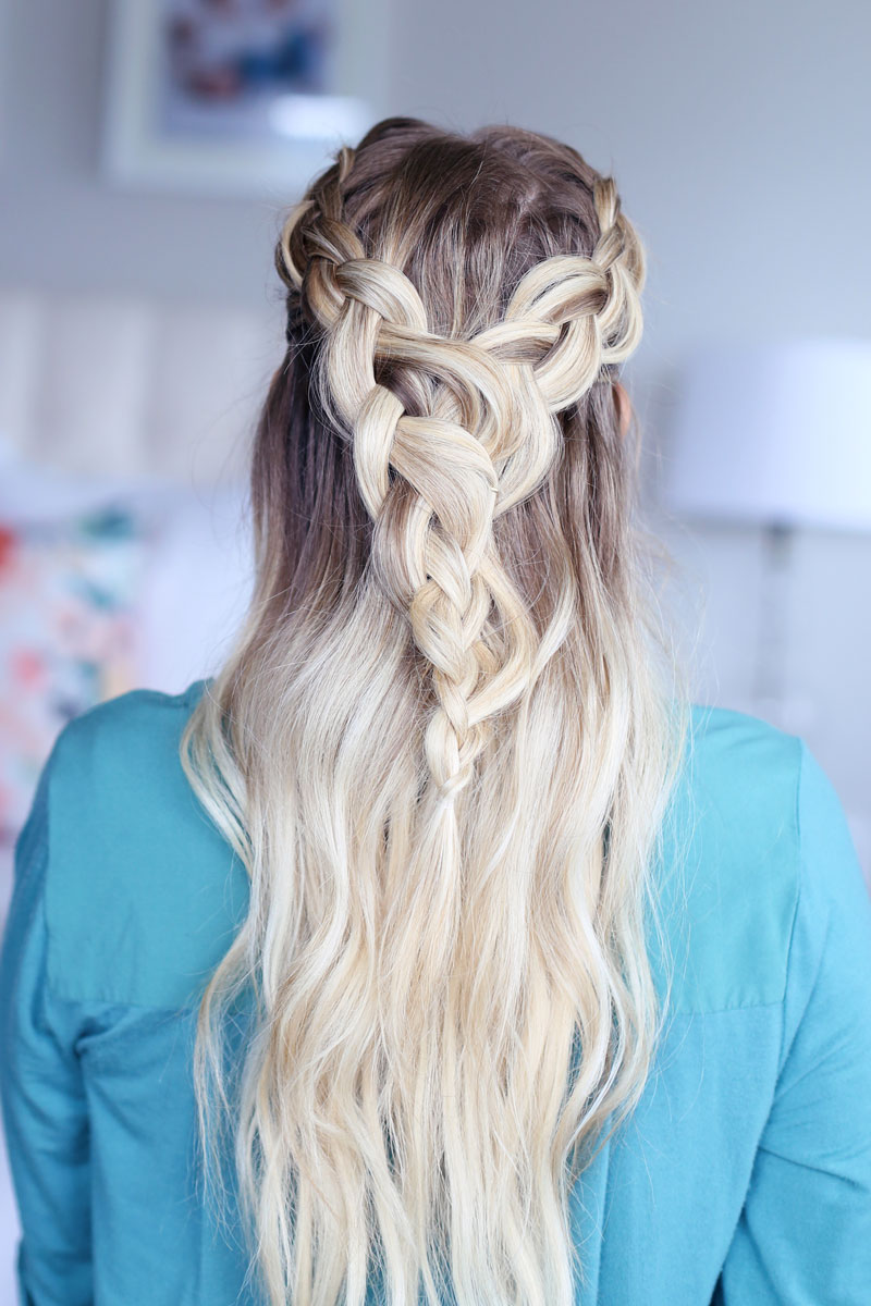 A close-up photo of a blonde woman facing away from the camera, her hair cascading down her back. Two braids come around each side of her head and meet at the back. Dutch braid hairstyles tutorial.
