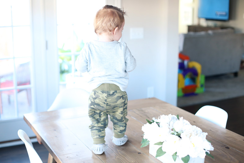 Toddler, standing on a dining room table.
