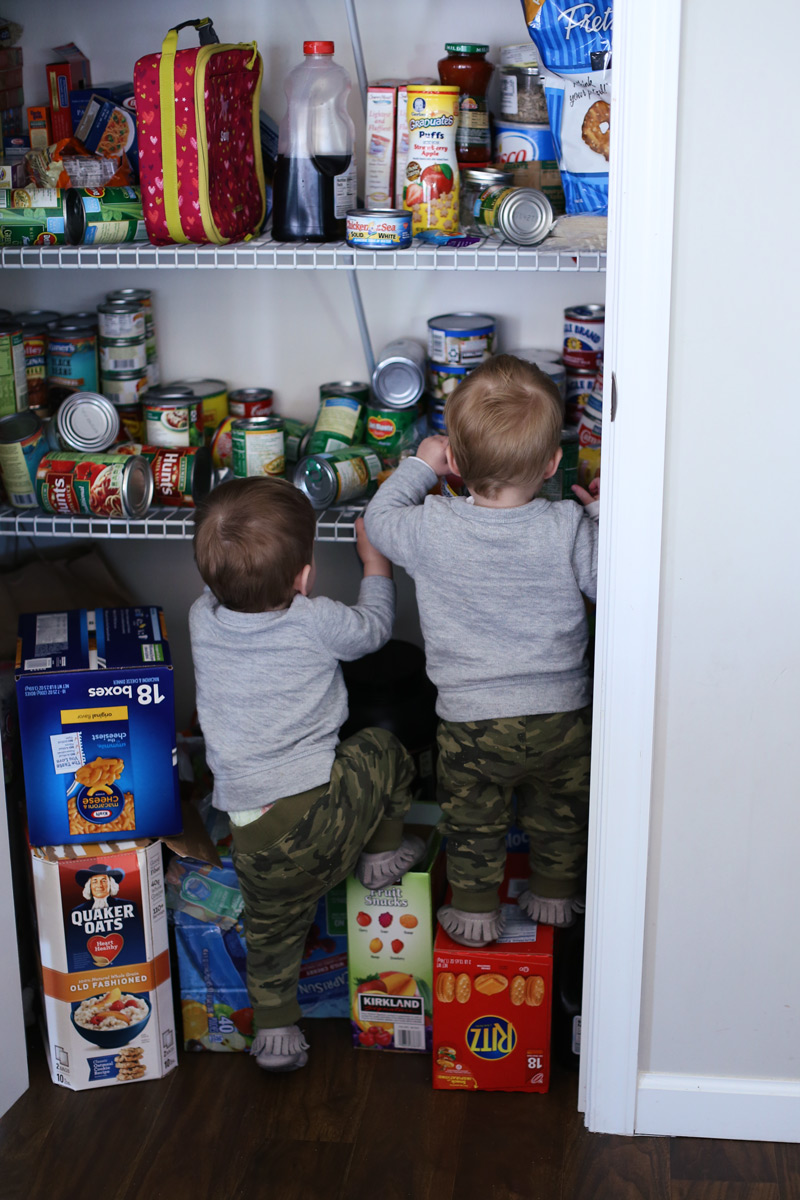 Two toddlers climb on boxes to explore shelves of tins and food.
