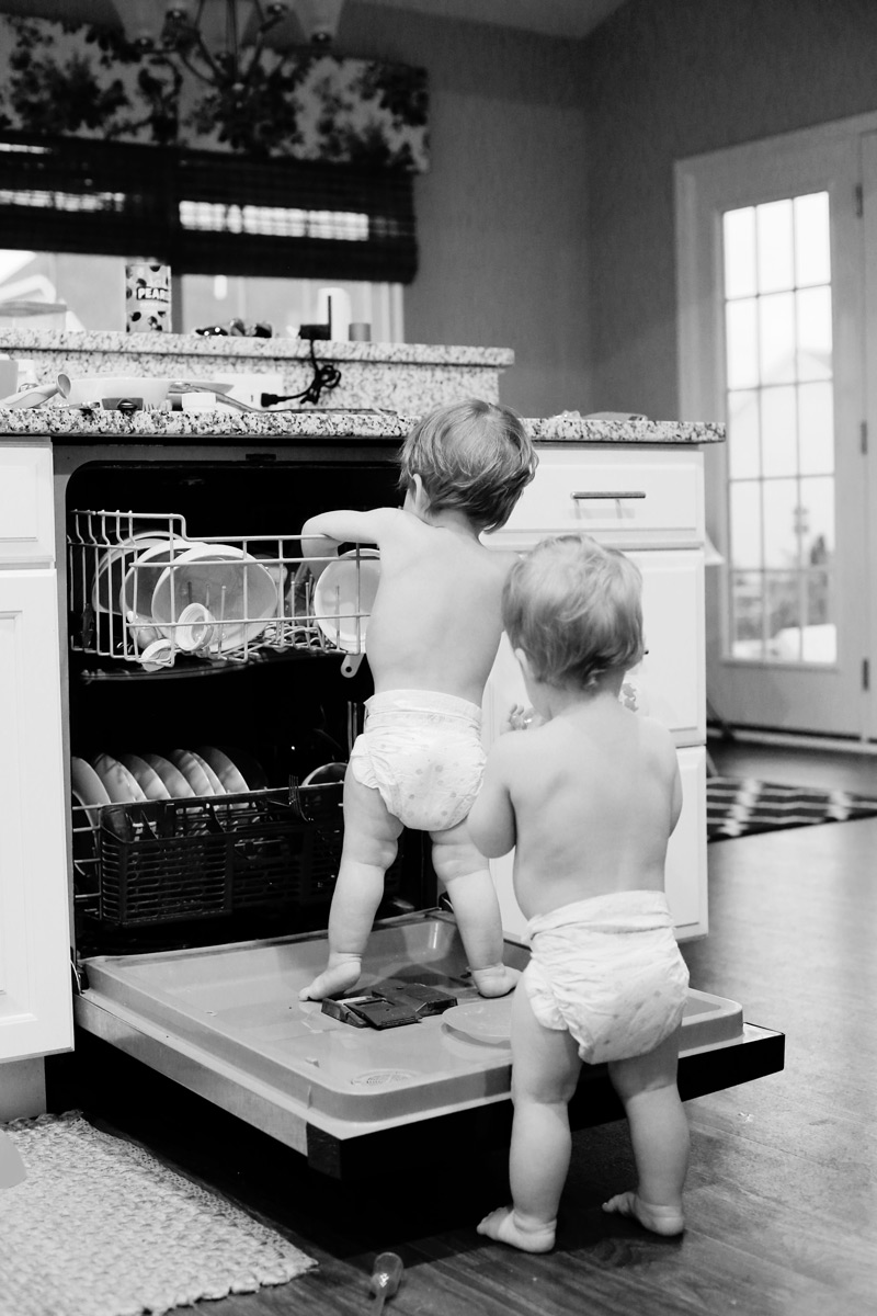 A sepia photo of toddlers in diapers loading a dishwasher.