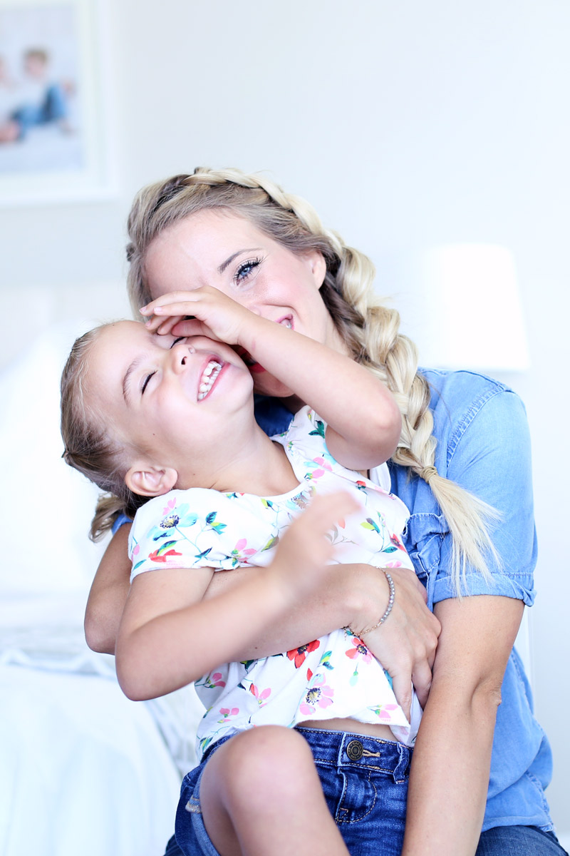 Abby sits with her daughter on their back, both laughing. Love your hair with Twist Me Pretty.