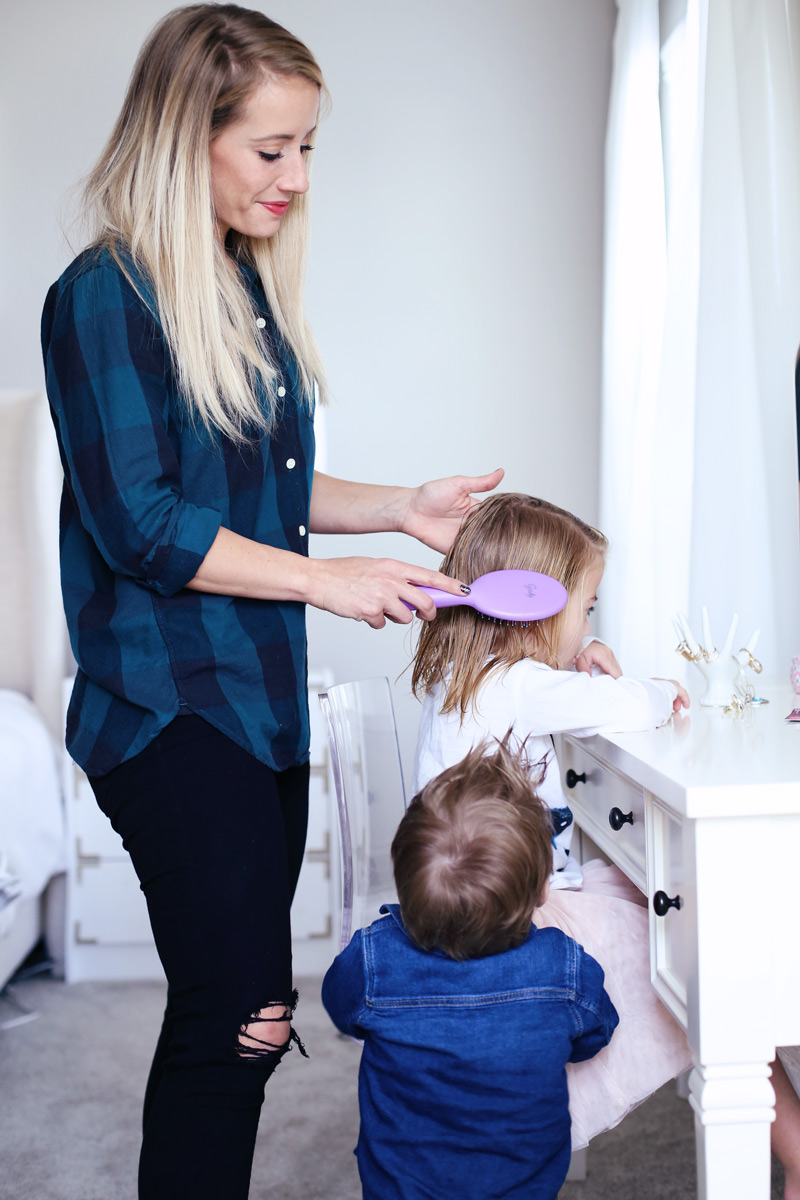 In a light room, a mother smiles as she brushes her daughter's hair while her son watches.