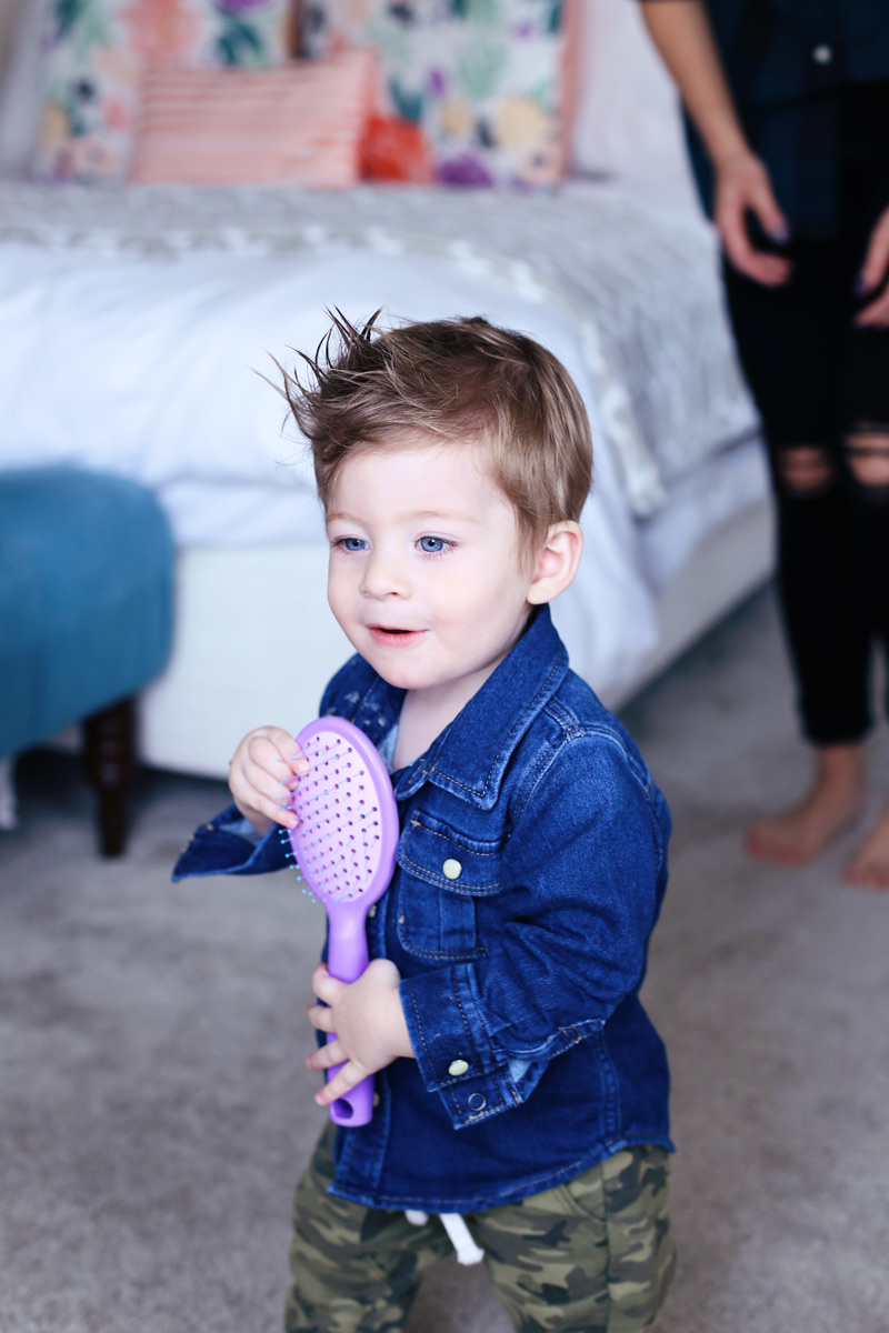 A little boy with bright blue eyes and a cowlick hair style smiles and holds a purple hair brush. Twist Me Pretty - Our Morning Routine.