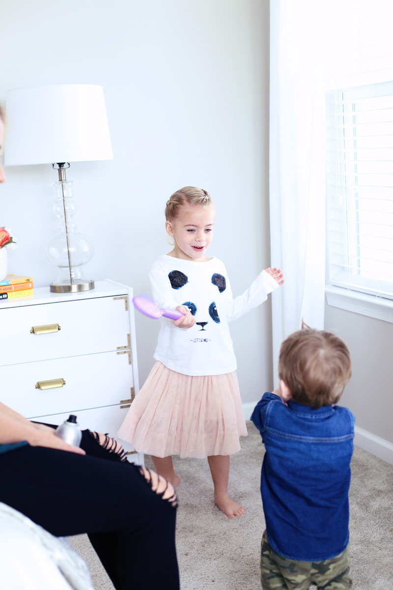 A little girl smiles and dances with a hair brush, looking at her little brother. Twist Me Pretty - Our Morning Routine.