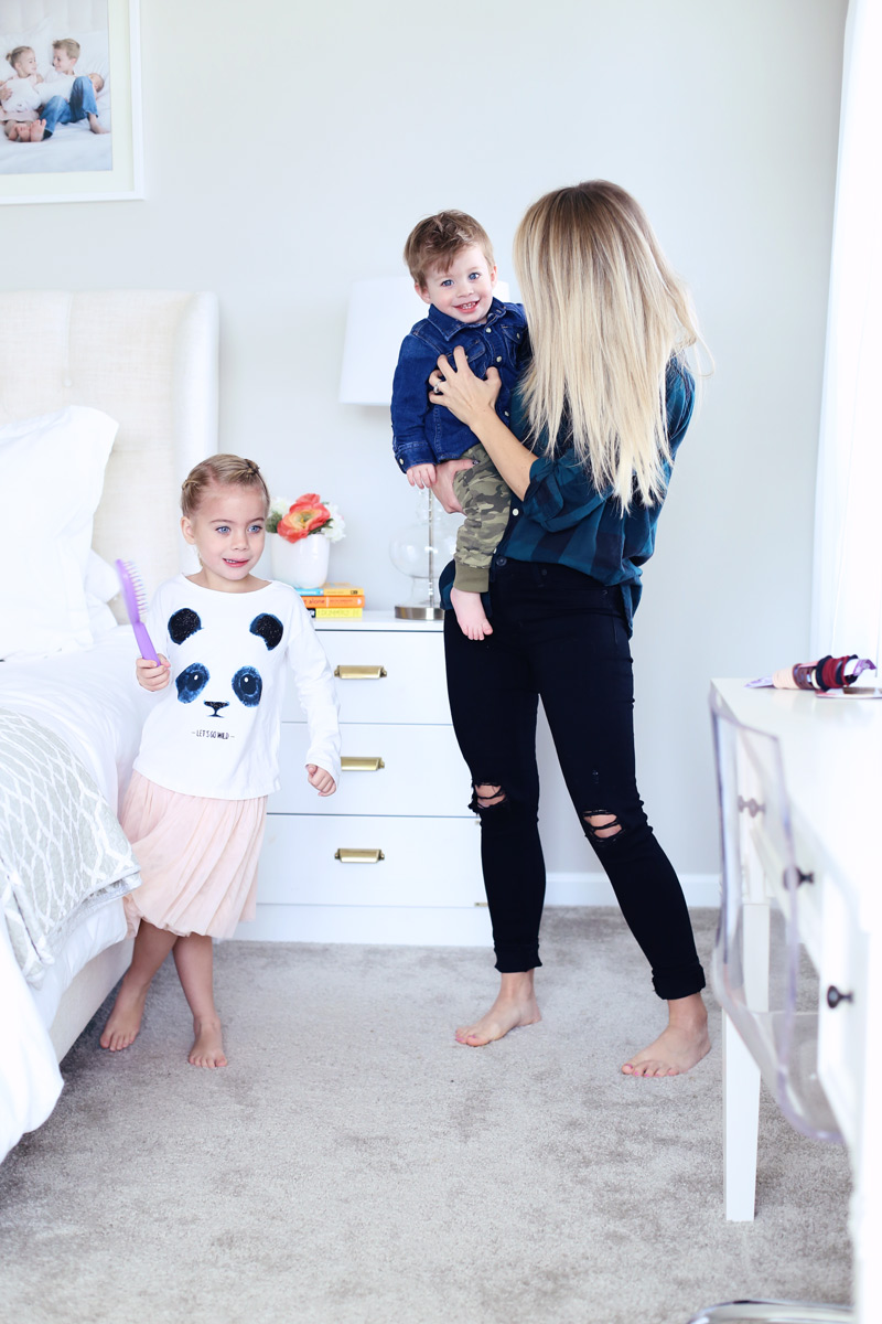 In a bedroom, a mother smiles at her son as he sits on her hip, while her daughter dances with a hairbrush. Twist Me Pretty - Our Morning Routine.