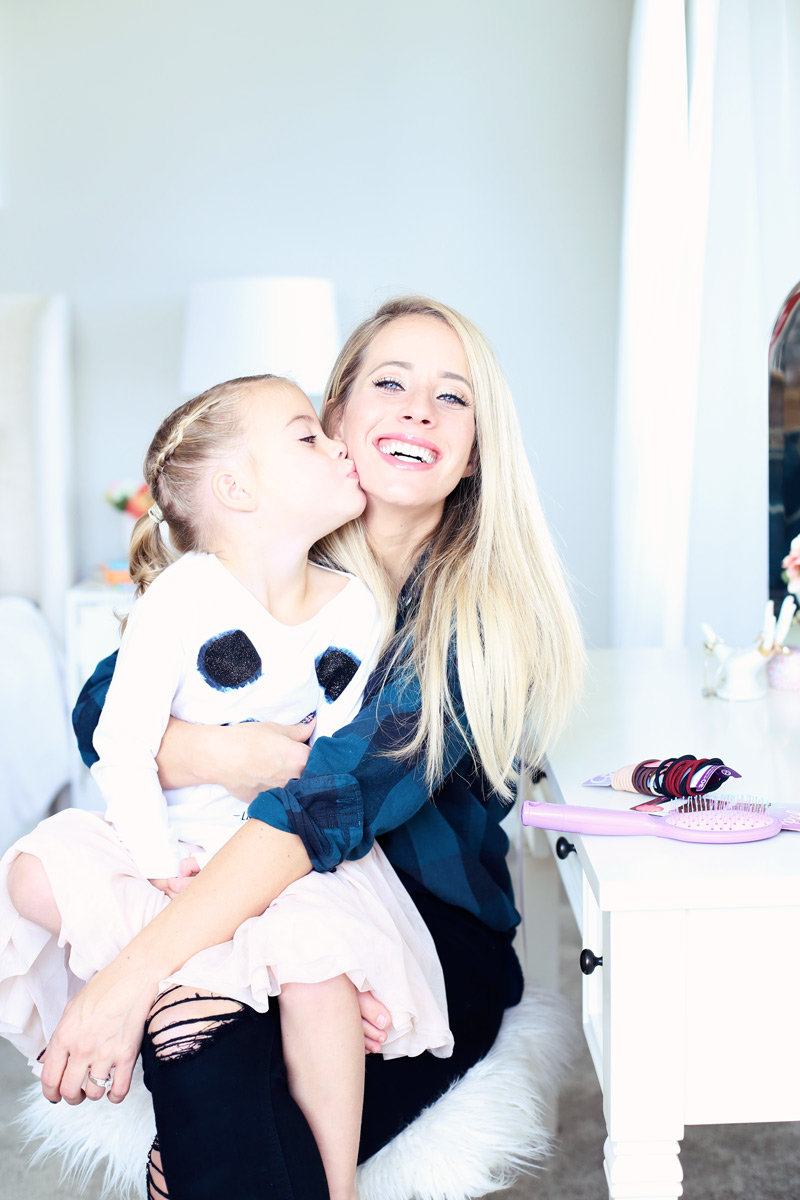 Special moments. A daughter sits on her mother's lap and kisses her on her cheek. Twist Me Pretty - Our Morning Routine.