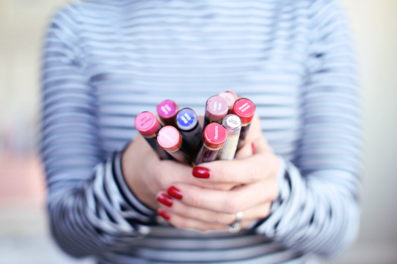 A woman holds out indelible lipstains in various colors. Twist Me Pretty.