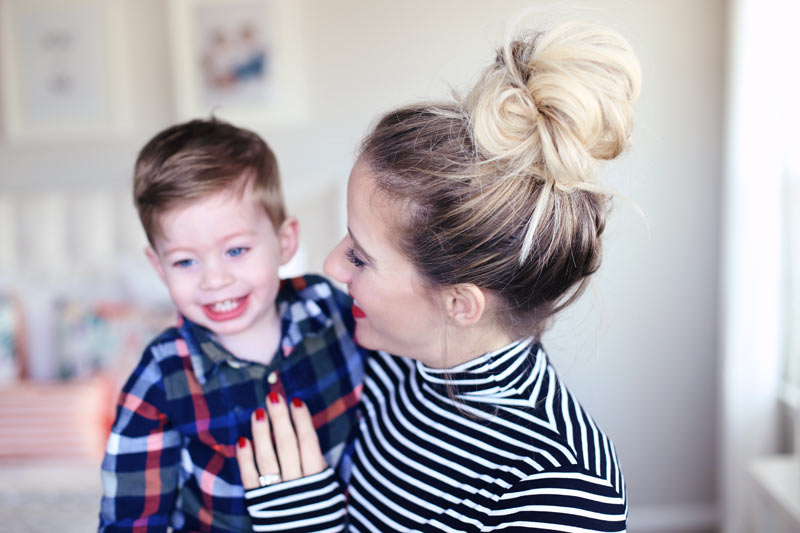 A mom with bright red lips and nails smiles proudly at her son. Twist Me Pretty.