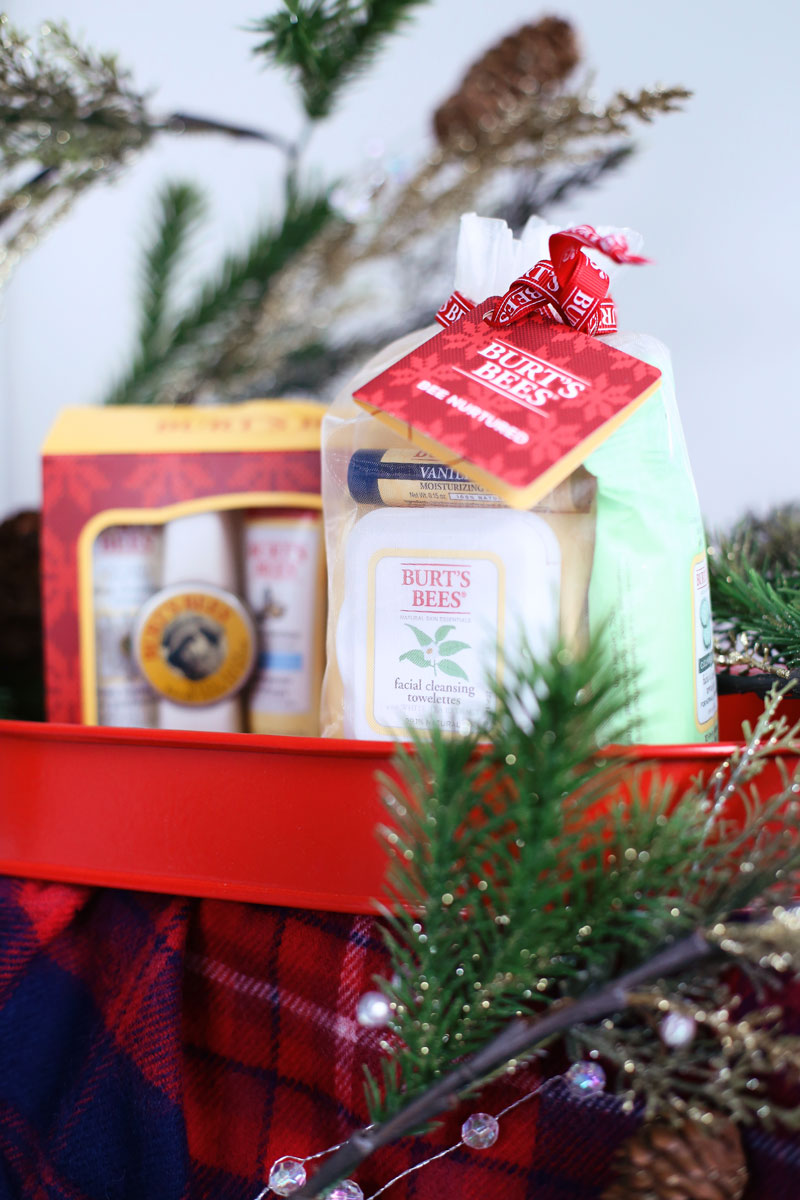 A festive photo of Burt's Bees' holiday gift sets on a tartan cloth with sprigs of festive pine trees. Find out at Twist Me Pretty.