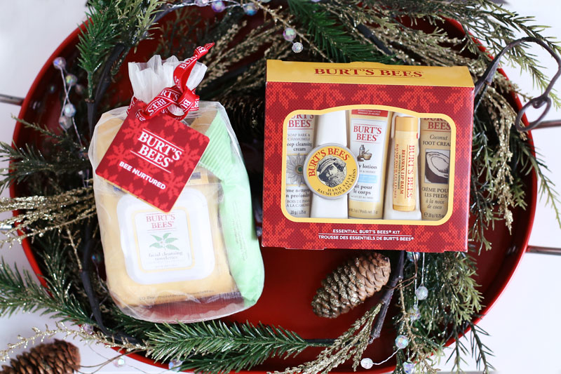 Burt's Bees' festive holiday gift sets, including the Bee Natural pack, sit in a red barrel surrounded by pine cones and leaves. Find out more at Twist Me Pretty.