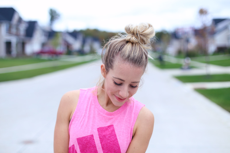 Looking down, a woman in a pink top smiles. She's staying in shape. Twist Me Pretty.