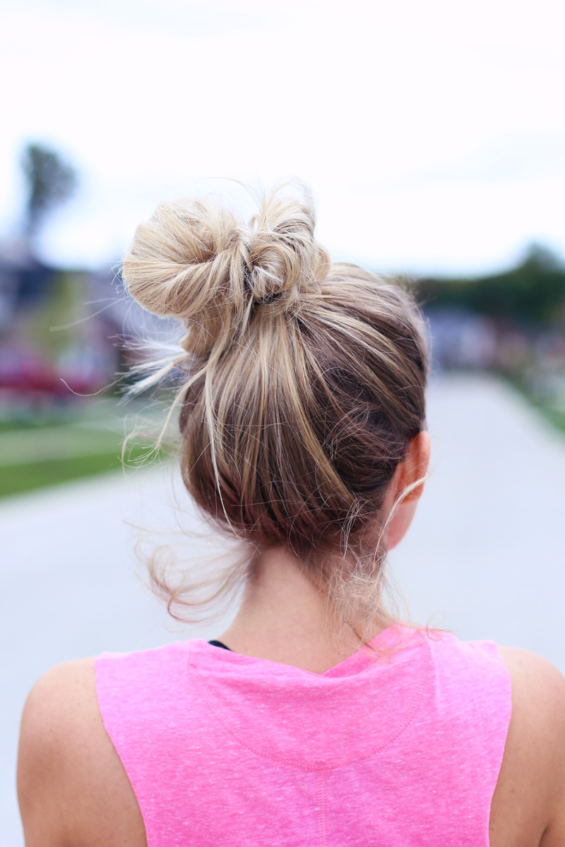 A woman looks away from the camera. We see her blonde top knot. The perfect hair style when you're staying in shape. Twist Me Pretty.