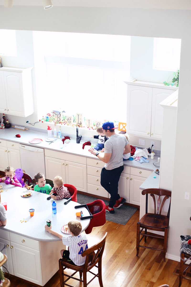 Aerial photo of a beautiful white kitchen, with several children sitting around a table.