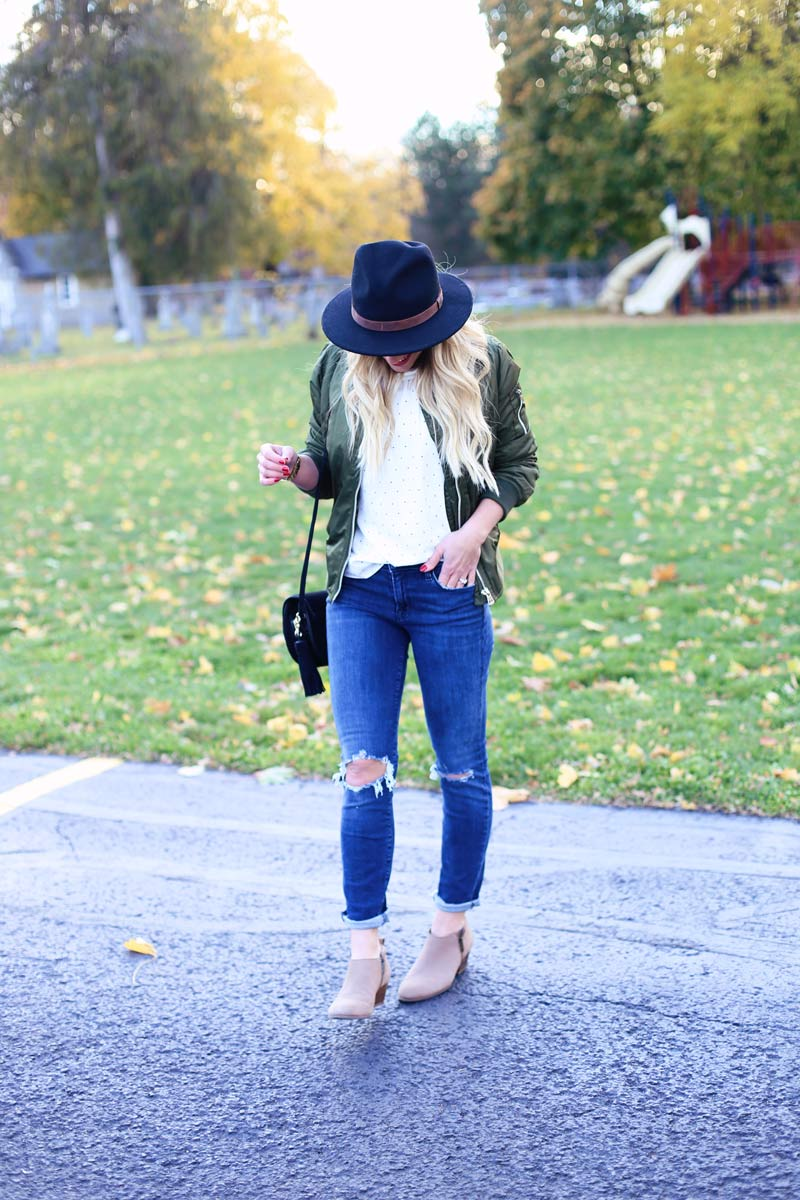 Twist Me Pretty's Abby wears stylish torn jeans, tan booties, and a hat.