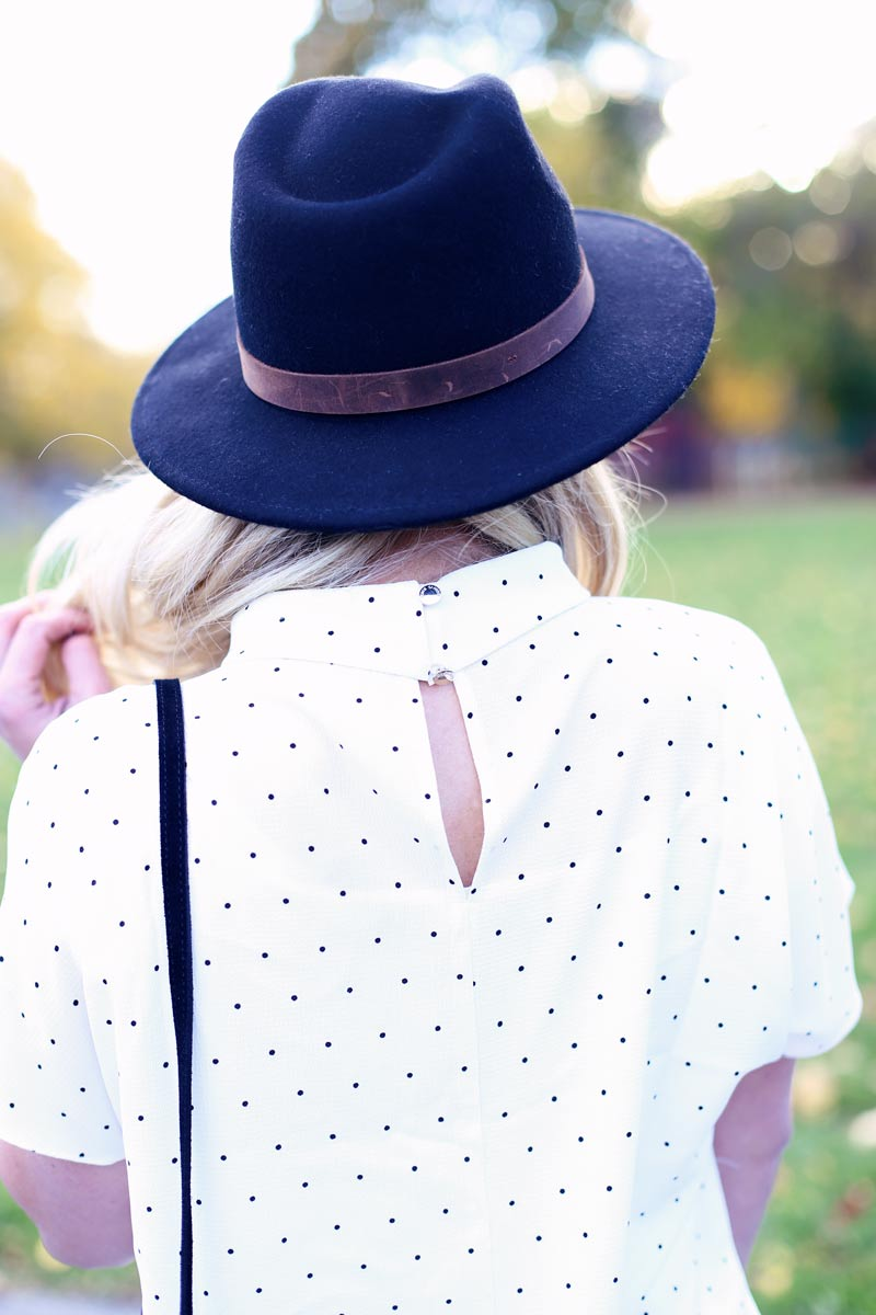 A black hat paired with a white, polka dot shirt - pretty.